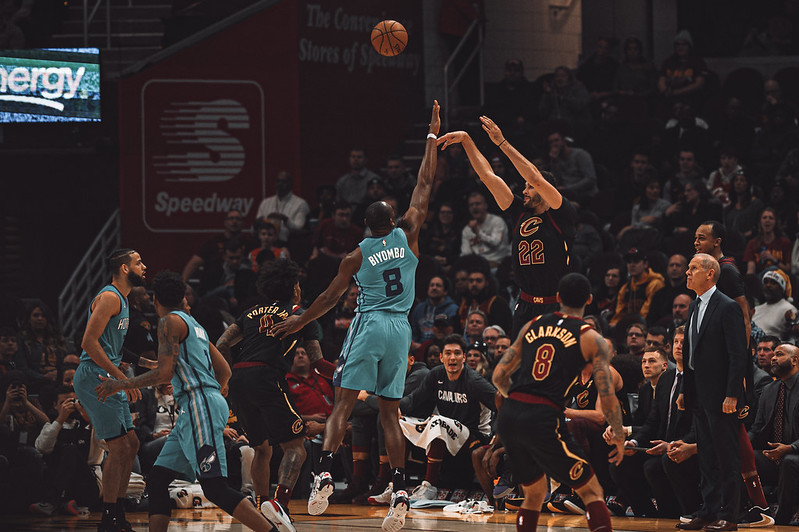 NBA Charlotte Hornets center Bismack Biyombo trying to block a shot against a Cleveland Cavaliers player.