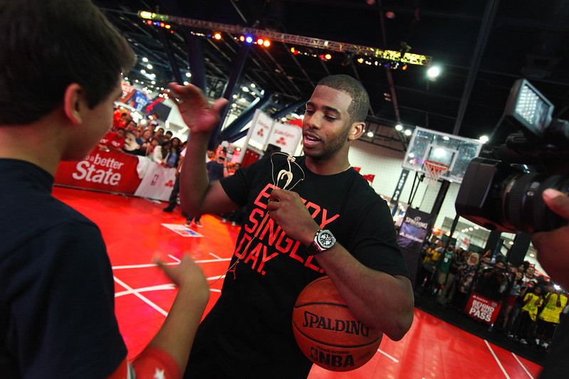 NBA point guard Chris Paul at the NBA All Star Jam Session congratulating a basketball fan.