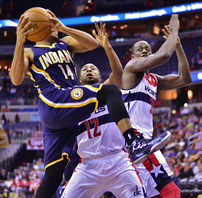 An Indiana Pacers player driving to the basket against two Washington Wizards defenders.