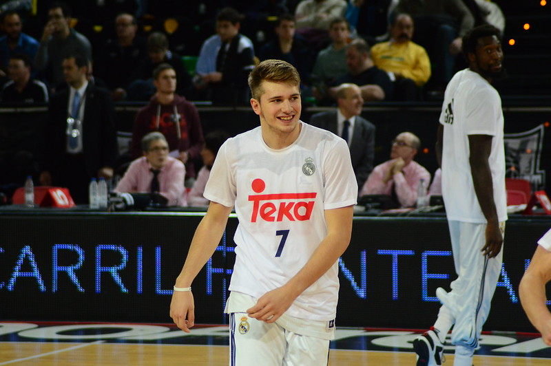 Point guard Luka Doncic smiling as he walks off the basketball court.