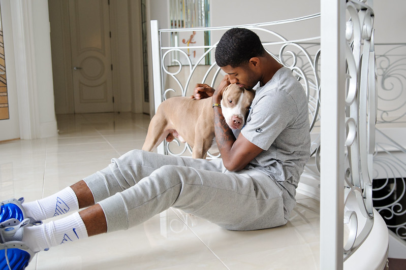 NBA superstar L.A. Clippers shooting guard Paul George at home on the floor with his dog.