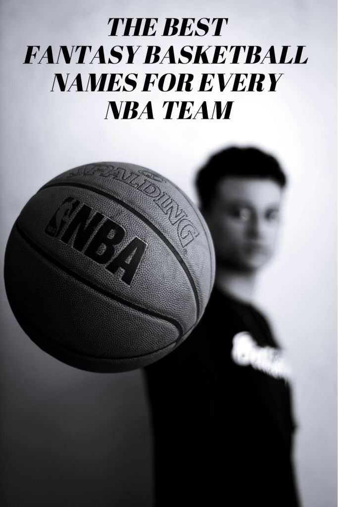 Grayscale photo of man holding NBA basketball.