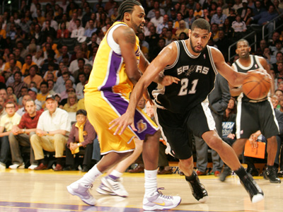 Legendary NBA San Antonio Spurs power forward Tim Duncan driving to the basket against a Los Angeles Lakers defender.