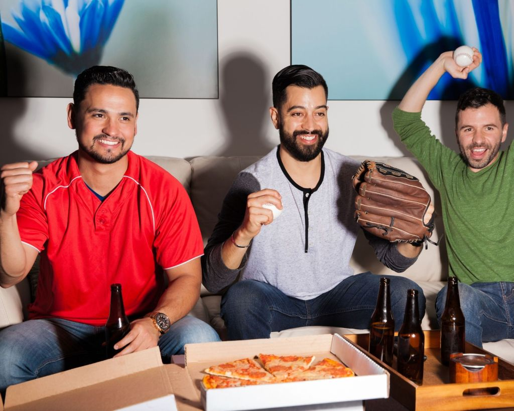 Guys watching a baseball game at home while eating pizza and drinking beers.