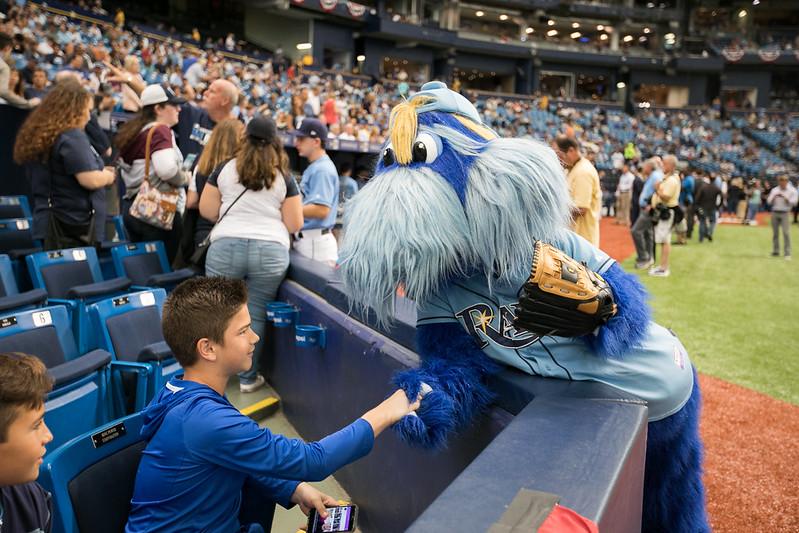 MLB Tampa Bay Rays mascot Raymond the Seadog shaking a boys hand at a baseball game.