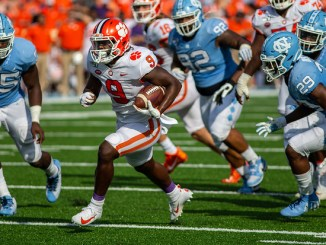 Clemson running back Travis Etienne running with the football against the University of North Carolina in a football game.