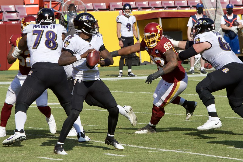 NFL Baltimore Ravens quarterback Lamar Jackson getting ready to throw the ball against a Washington Football Team pass rush.
