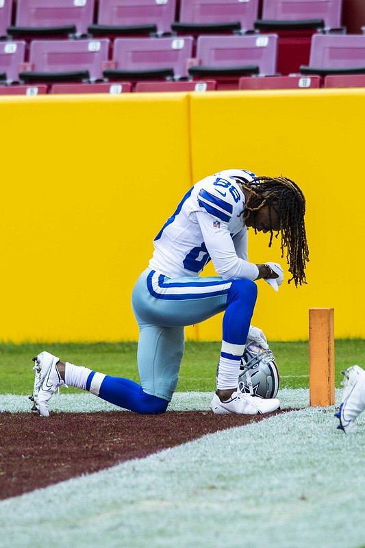 Dallas Cowboys wide receiver CeeDee Lamb down on one knee in  the endzone during a football game.