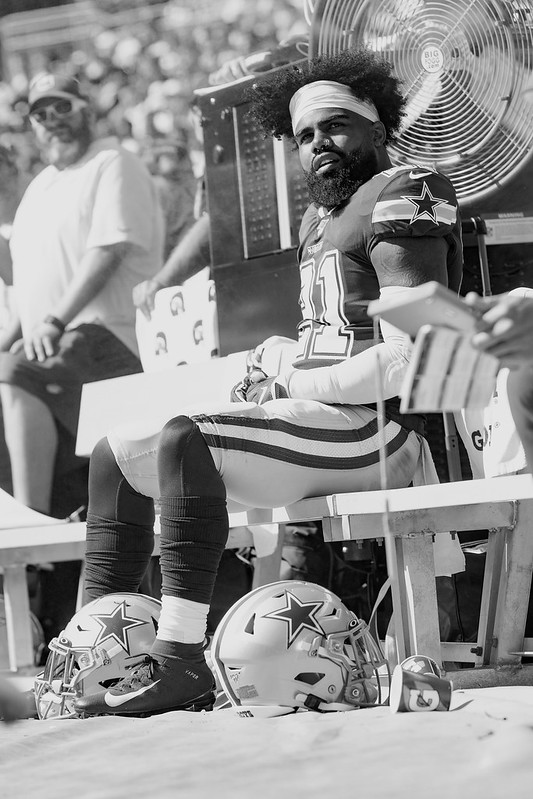 Dallas Cowboys running back Ezekiel Elliott sitting on the bench during a football game.