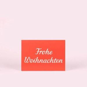 """Postkarte """"Frohe Weihnachten"""" von krima und isa, roter Hintergrund, weiße Schrift"""