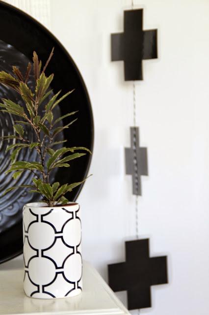 schwarze Kreuzkette und grafischer Übertopf mit Pflanze