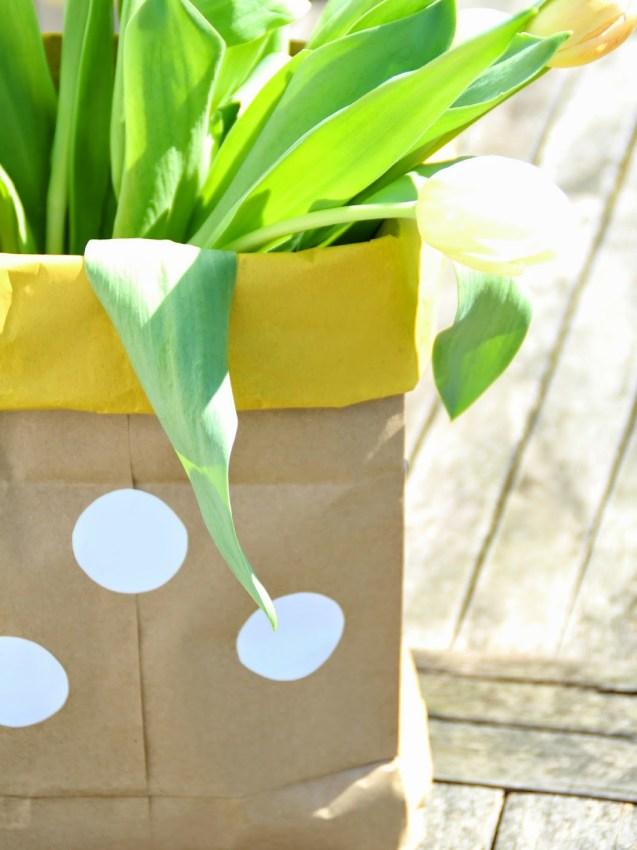 Braune Paperbag mit gelbem Rand und weißen Punkten als Vase für Tulpen