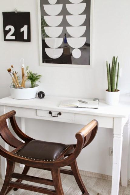 Schreibtisch in Weiß mit antikem braunen Hocker davor Im Hintergrund Blumenampel als Pinselhalter