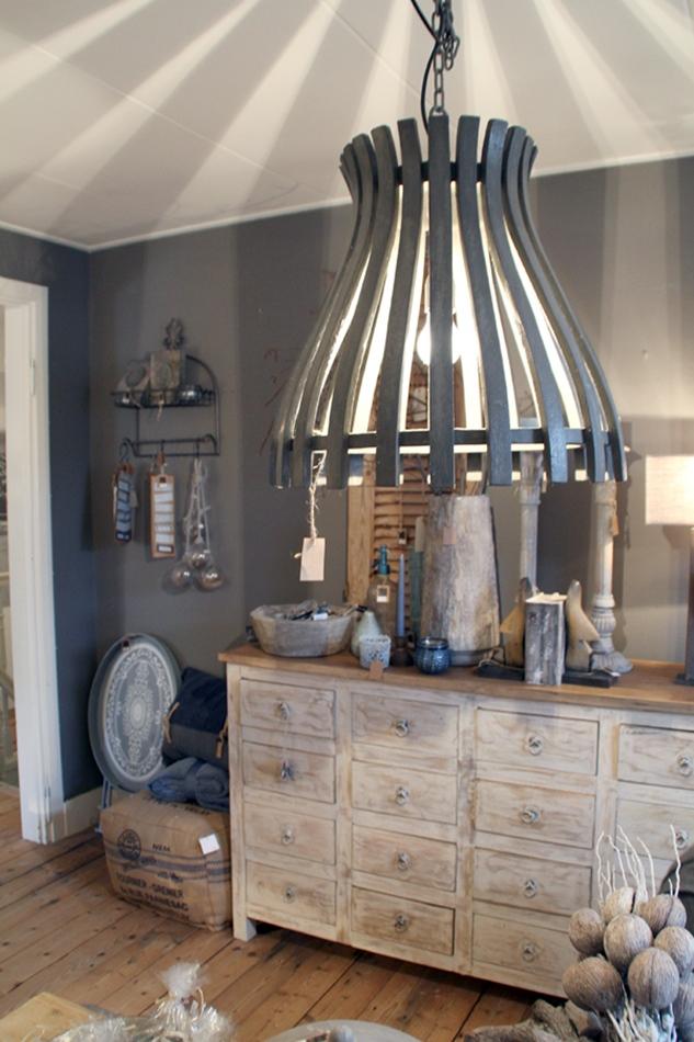 Riesige graue Lampe aus Holzplanken mit Kommode und Wohnaccessoires im Hintergrund in geige-grau