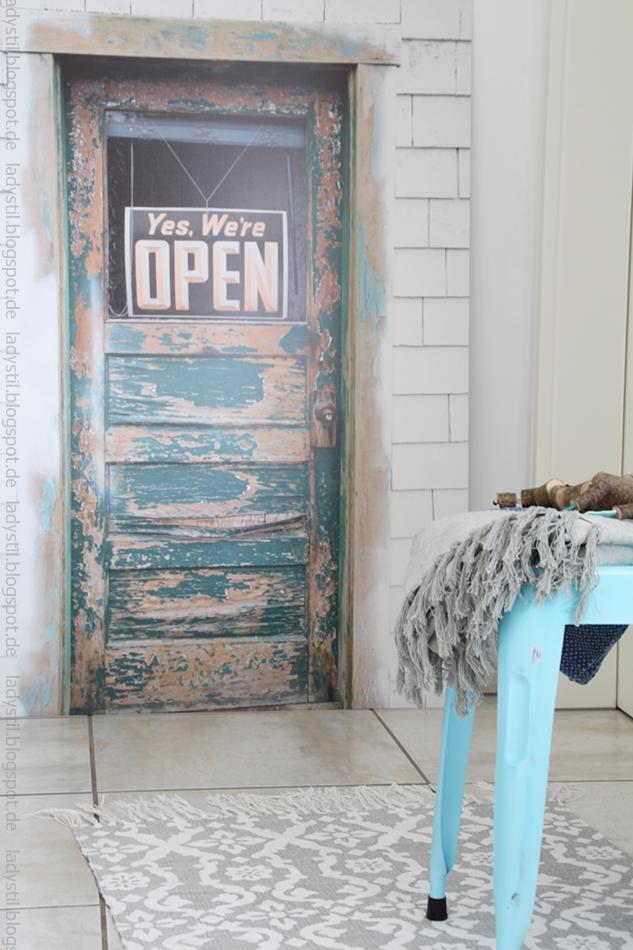 türkiser Hocker mit beigem Plaid vor einem Poster das eine Vintage-Tür zeigt