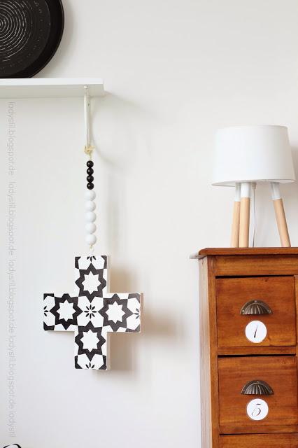 Kreuzkette hängt an einem weißen Regal die Kommode daneben ist holzfarben