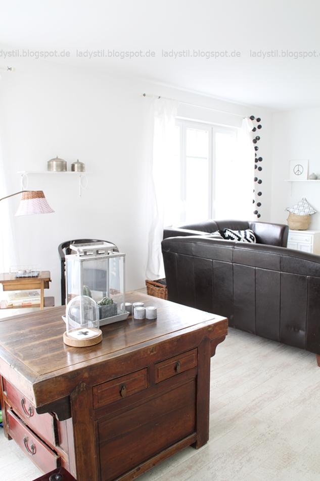 Sicht auf eine große viereckige Kommode mitten im Wohnzimmer mit Glaskuben und Pflanzen