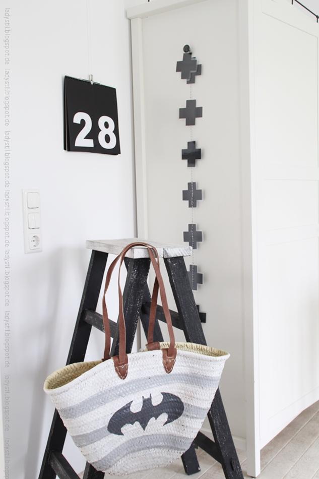 Korbtasche weiß hellgrau gestreift mit großem anthrazitfarbenem Batman Emblem hängt an einer kleinen schwarz weißen Leiter schwarz weißer Kalender im Hintergrund für den Bloggeroptimierungsfotowettbewerbbeipixum