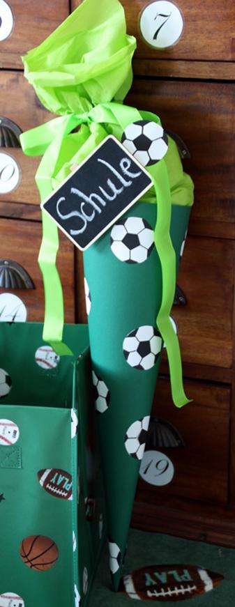 """grüne Schultüte mit Fußbällen aus Bällen beklebt und einem kleinen Tafelschild mit Schriftzug """"Schule"""" steht auf einem Badetuch mit Fußballmotiv, daneben eine Aufbewahrungsbox mit Fußballmotiven"""
