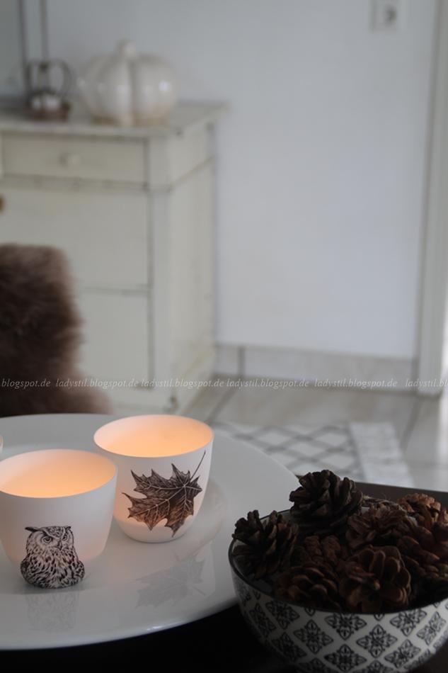 zwei brennende Teelichter und Tannenzapfen, im Hintergrund Kommode mit Herbstdeko