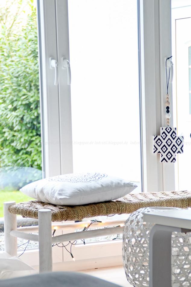 Bast-Sitzbank mit großem weißen Bast-Windlicht vor einem lichtdurchfluteten Fenster