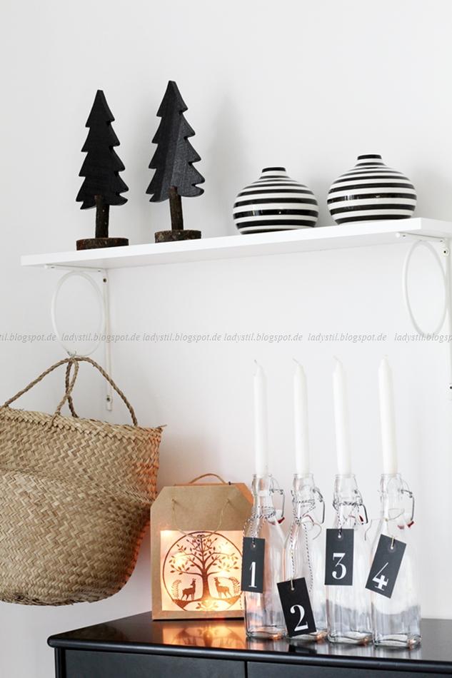 Lichtertüte auf einer schwarzen Kommode mit schwarzen Tannenbäumen aus Holz