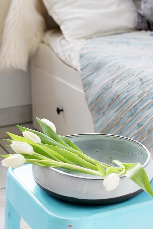 Blick auf einen türkisen Hocker mit einer Schale voller liegender Tulpen