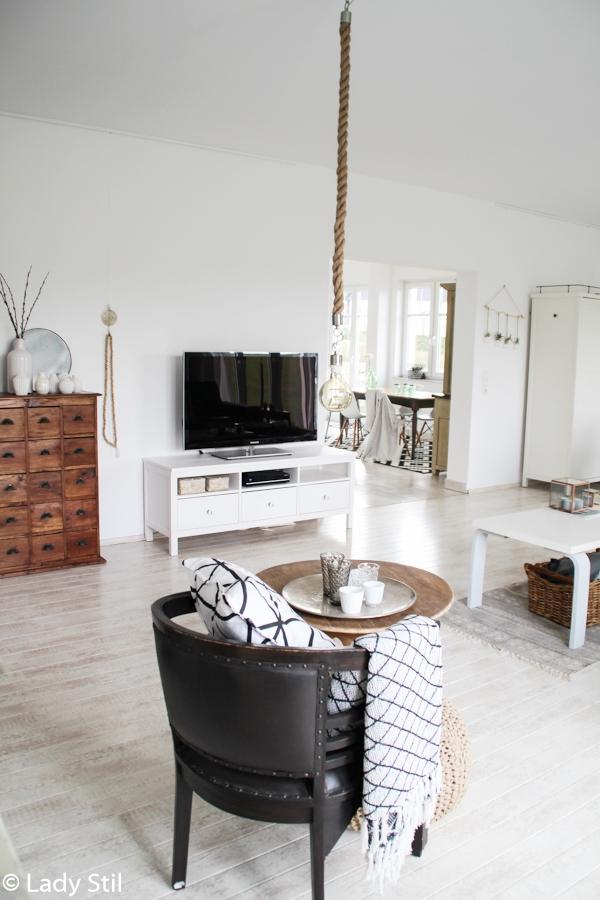 Blick ins Wohnzimmer weiße und holzfarbene Dekoelemente