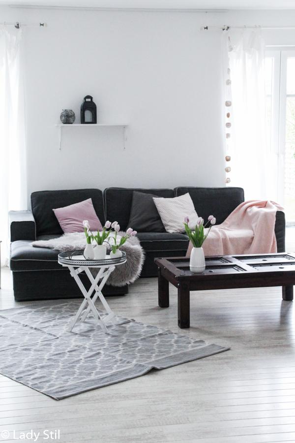 wie man mit wenigen Mitteln ein monocromes Zuhause in ein frühlingshaftes, fröhliches Interior-Ambiente verwandelt, Wohnzimmer Sofa mit rosa Kissen und Plaid