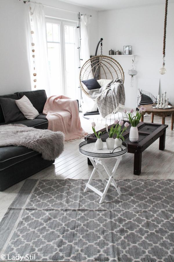 wie man mit wenigen Mitteln ein monocromes Zuhause in ein frühlingshaftes, fröhliches Interior-Ambiente verwandelt, Wohnzimmeransicht mir Hängesessel, grau-weißem Teppich, Plaid in Blush