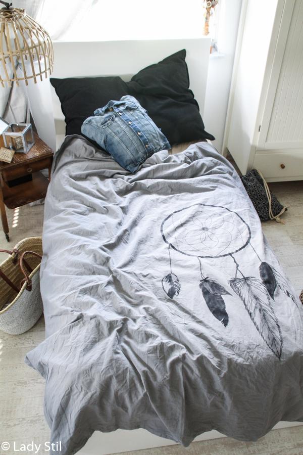 Einblick Schlafzimmer mit grauer Bettwäsche, auf der ein selbstgemalter Traumfänger abgebildet ist