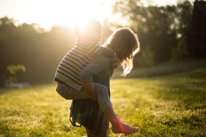 Little girl carrying little boy outside in the sun.