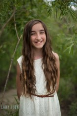 glamour-portrait-younge-girl-smiling-at-the-camera-in-the-trees