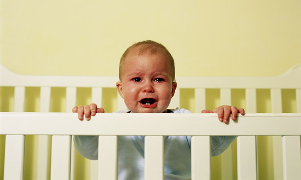 Baby crying in its cot, teething