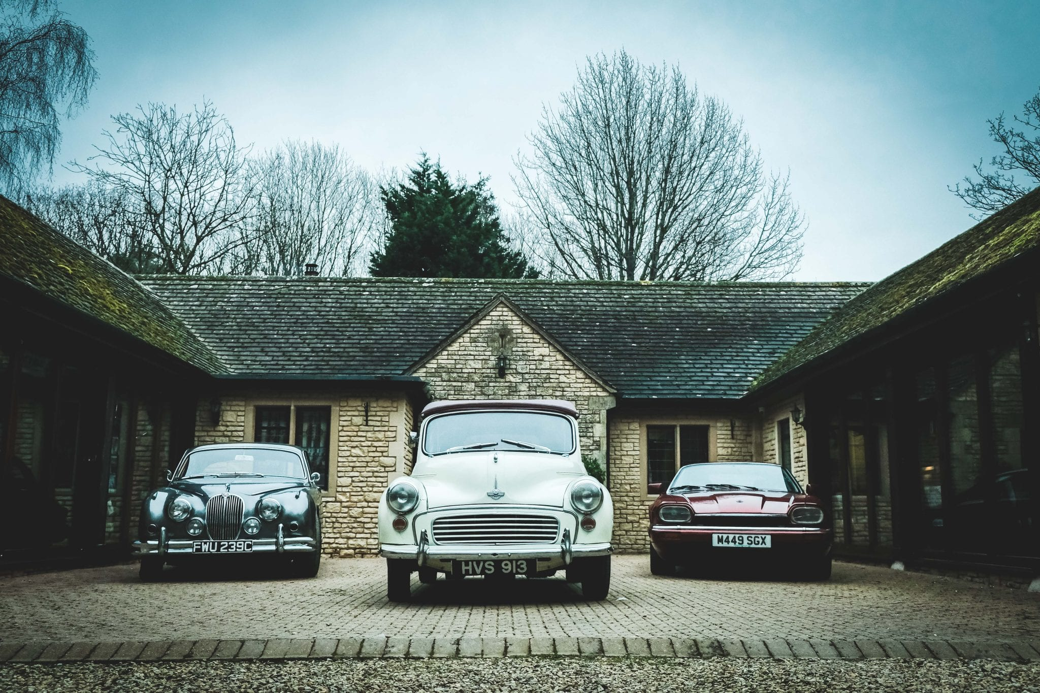 Classic cars parked outside Lady's Wood Shooting lodge for a corporate entertainment day