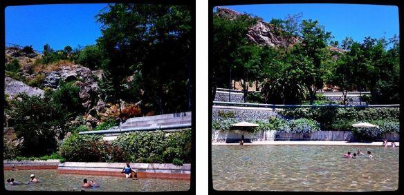 El parc de la Creueta del Coll. Piscina con algunas personas nadando. Montaña y jardines al fondo.