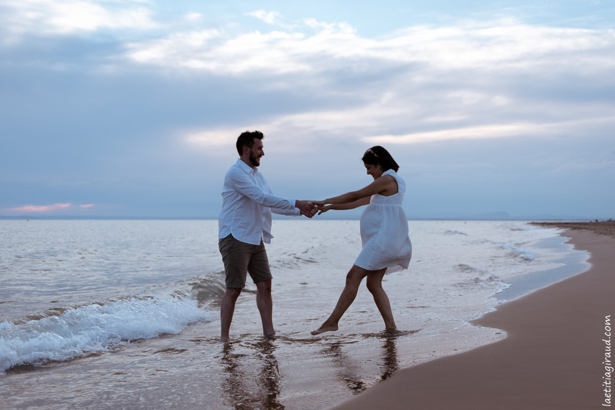couple dans la mer avec ventre femme enceinte