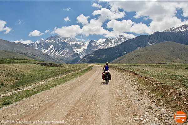 Rider on a gravel track, mountains in background
