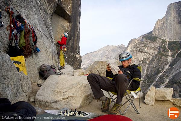 Grimpeur assis étudie le topo. Autre grimpeur qui assure-Yosemite