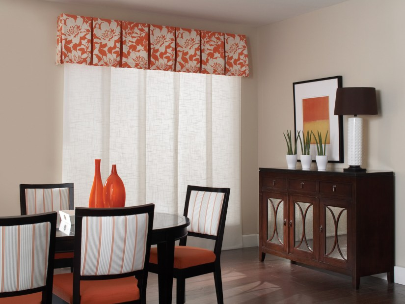 Genesis Panel Track Shades pair with a coral floral valance and striped dining room chairs.