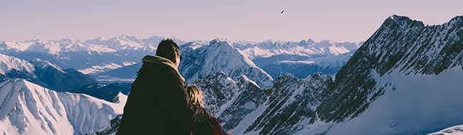 Couple wrapped in blanket looking at snowy mountains | Physical Health Links | Lafayette Couples Therapy | Lafayette, CA 94549