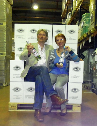 George Rowley and Marie-Claude Delahaye sitting on a chair made from boxes of La Fée blanche absinthe