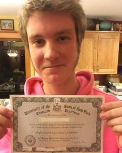 Lagom Landing Student poses with his High School Equivalency certificate, earned during his gap year.