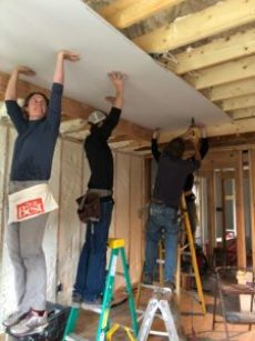 Lagom Landing Gap Year Students and Staff Do It Best, working together to hang dry wall.