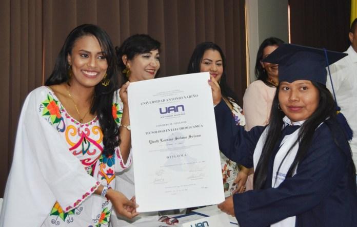 La coordinadora de bienestar estudiantil, Blanca Paola González, le hace entrega título de profesional a Loraine Yiceth Solano.