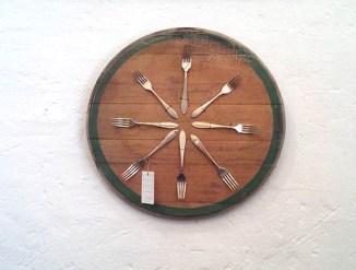 Medallon decorativo con tenedores de alpaca antiguos sobre tapa de barrica vino
