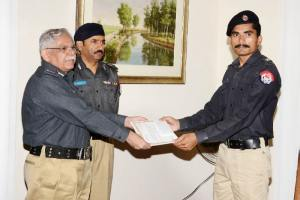 igp is giving reward to a cop,dig rai tahir is also present at the occasion