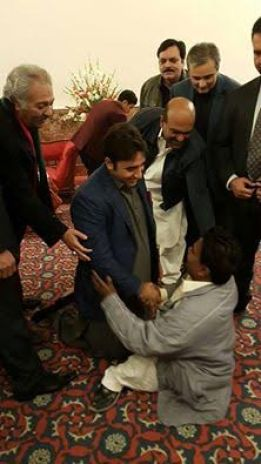 Chairman Bilawal Bhutto Zardari sitting on the ground while shaking hand with a disable Jaiyala in Faisalabad
