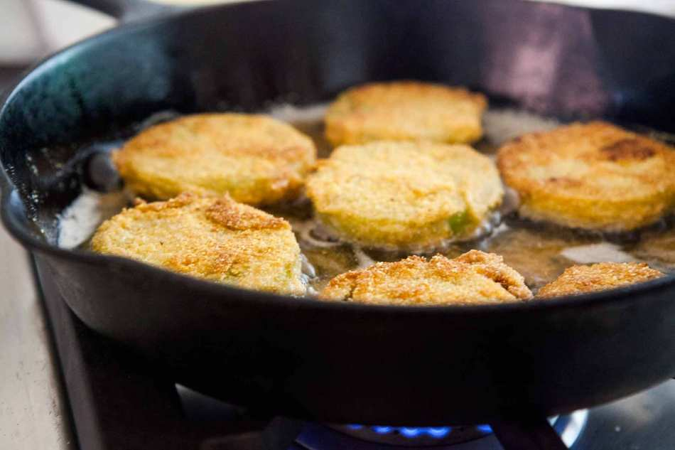 fried green tomatoes cooking in a pan
