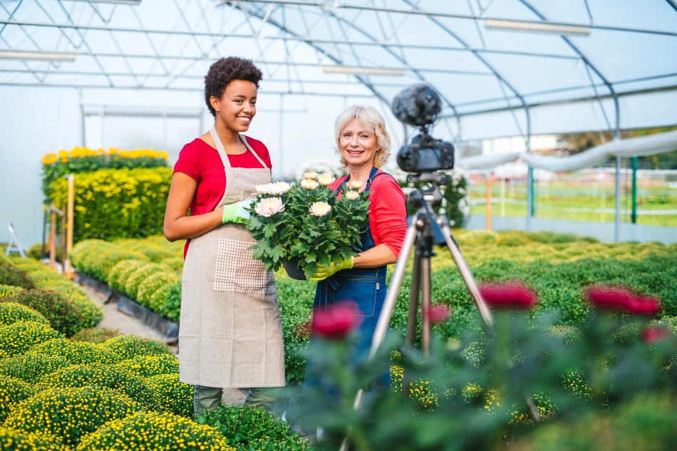Two women gardeners standing in front of a camera.